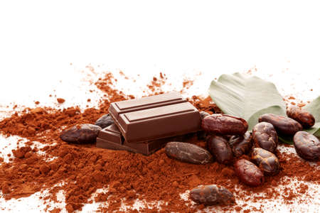 Composition with cocoa powder, beans, chocolate and  leaves on white background.