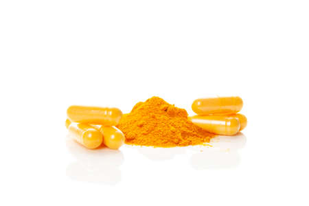 Turmeric (curcumin) powder heap and capsules isolated on white background. Anti-inflammatory nutritional supplement. Stok Fotoğraf