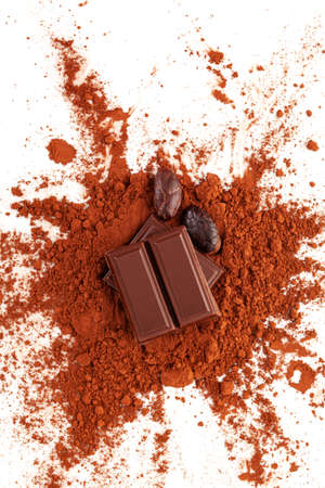 Dark chocolate background with cocoa beans and powder, top view. Stok Fotoğraf