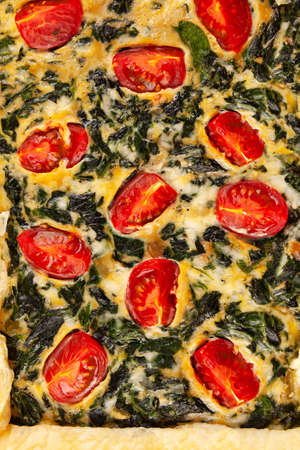 Detail of spinach pie or quiche with cheese and tomatoes from above.