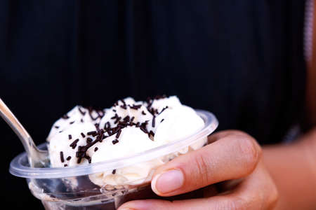 Woman holding cup with chocolate mousse and cream. Profiterole, take away dessert. Stok Fotoğraf