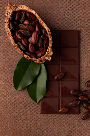 Delicious dark chocolate background. Chocolate bar, cocoa beans and  leaves on table, flat lay.