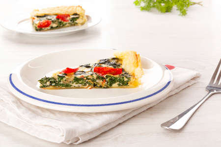 Piece of pie with spinach and tomatoes. Culinary vegetarian food.