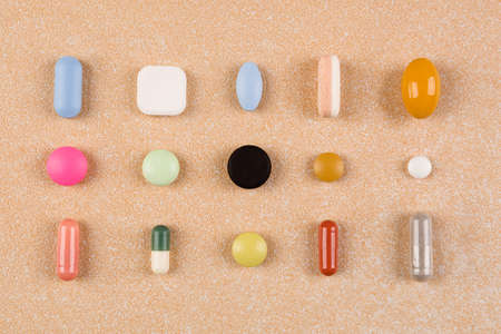 Various colorful pills, capsules and tablets, flat lay. Vitamins, perscription drugs, painkillers, nutritional supplements and antidepressants. Big Pharma.