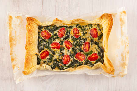 Vegetarian spinach pie or quiche with cheese and tomatoes on white wooden background from above.