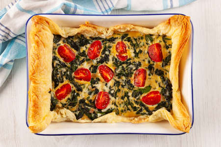 Vegetarian spinach pie or quiche with cheese and tomatoes in a baking dish from above. Stok Fotoğraf