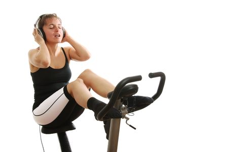 Woman on spinning bicycle with headphones listening music Stock Photo - 3663412