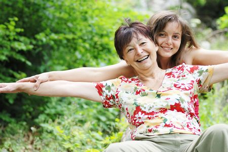 Mature woman has happy time with her daughter in nature photo