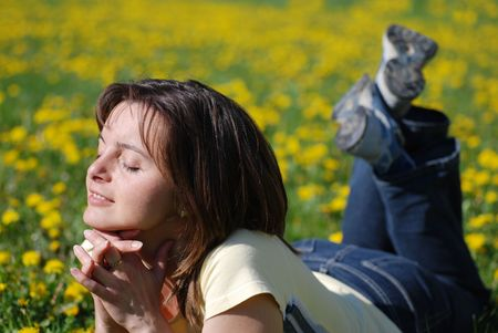 Woman lying in field of dandelions with face turned to sun Stock Photo - 3663420