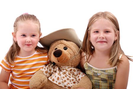 Studio portrait of two sister with bear toy - isolated photo