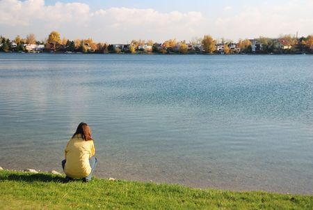 crouches: Woman crouches at lake and looks to beautiful fall nature