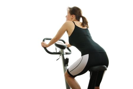 Isolated young woman riding on a spinning bicycle from back                                 photo