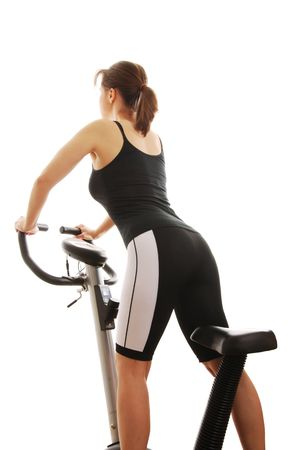 Isolated young woman standing on a spinning bicycle from back photo