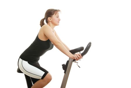 sportswoman: Isolated young womanexercising on a spinning bicycle - profile Stock Photo