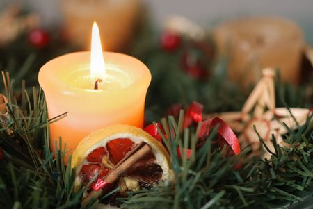 advent: Detail of christmas advent wreath with burning candle. Focus on candle.