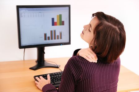 head pain: Business woman with neck pain. Focus on hand on neck with blurred monitor on table in background.