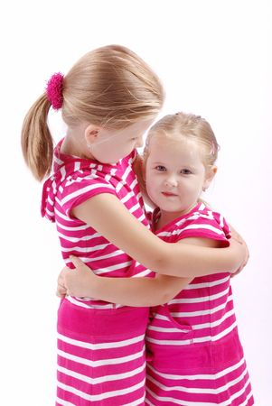 embracement: Studio portrait of cute little girls (sisters) - isolated