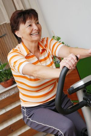 Senior woman exercise on spinning bicycle at home - diagonal composition                       photo