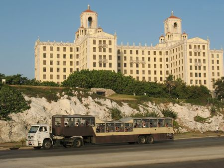 Special cuban transport mean - Camelbus driving in the Havana street in Vedado and behind is hotel nacional photo