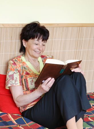 Smiling senior woman reading book in her room Stock Photo - 3703762