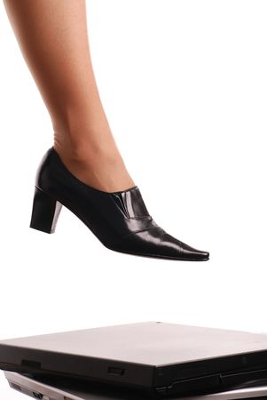 Leg of woman in elegant shoe stepping on computers - isolated on white background photo