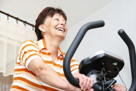Senior woman exercise on spinning bicycle at home photo