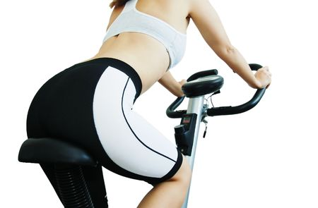 stationary bike: Isolated young woman riding on a spinning bicycle Stock Photo