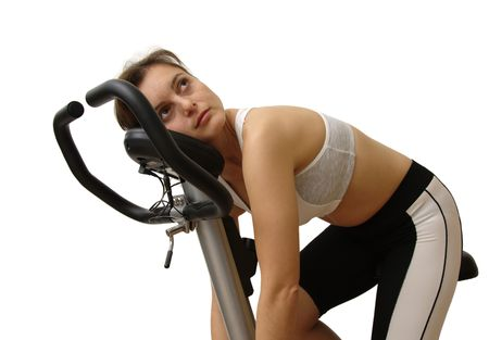 Isolated tired young pretty woman siting on spinning bicycle Stock Photo