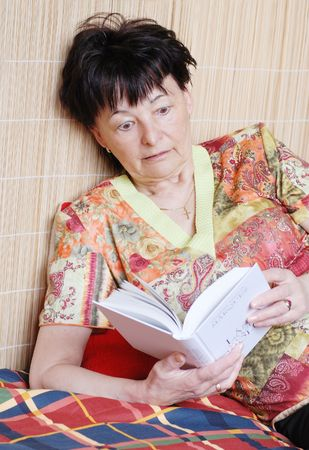 thriller: Senior woman reading thriller book in her room