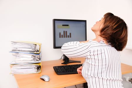 Business woman with neck pain sits on workplace with documents and monitor on table Stock Photo - 3844582