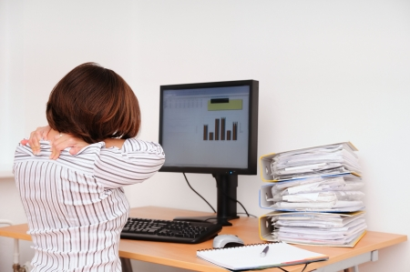 Business woman with neck pain sits on workplace with documents and monitor on table Stock Photo - 3844579