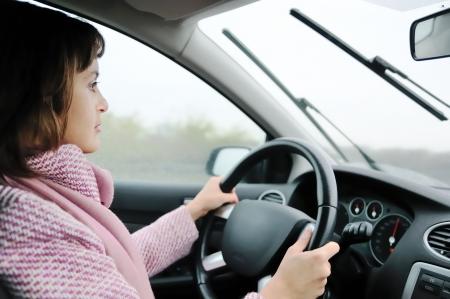 ruitenwisser: Young Business vrouw rijden auto in de regen (focus op gezicht) Stockfoto
