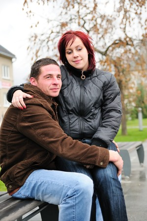 Woman sits on knees of man outdoors - romantic scene photo
