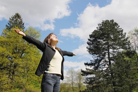 hand lifted: Woman is  enjoying her life outdoors among trees on sun