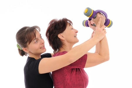 assisted: Senior woman  exercising with barbells assisted by trainer