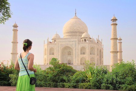 monument in india: Young tourist woman admires Taj Mahal