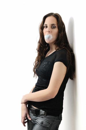 Beautiful teenage girl (woman) making bubble with chewing gum isolated on white background