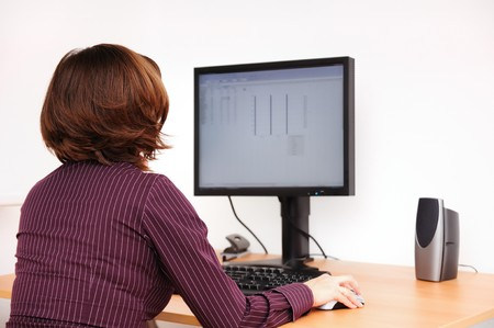 speakers: Business person works at table with computer