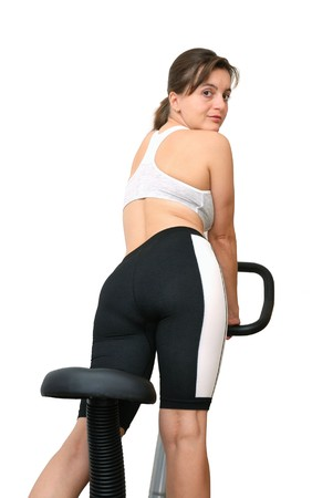 stationary bike: Isolated young woman standing on a spinning bicycle and looking over shoulder