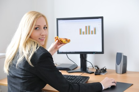 Young smiling business person working with computer eating pizza Stock Photo - 4534190