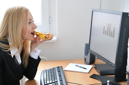 unhealthy snack: Young business woman siting at work table and eating pizza