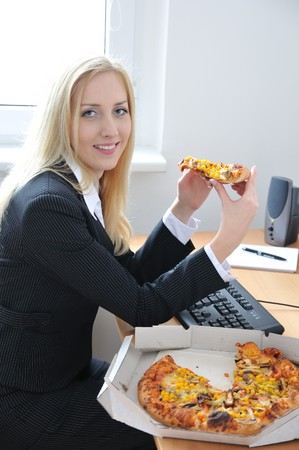 unhealthy lifestyle: Young smiling business person on work place eating pizza Stock Photo