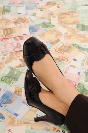 under control: Crossed legs on banknotes (money under control and security concepts)          Stock Photo