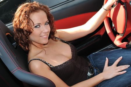 Young beautiful smiling woman sitting in sport car - red interior detail photo
