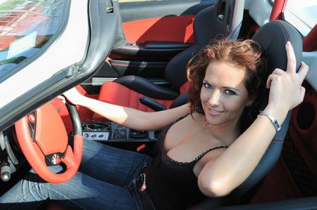Young beautiful smiling woman sitting in sport car - red interior detail