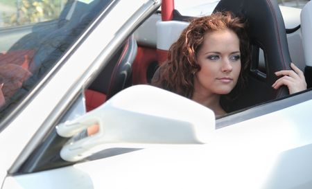 Young beautiful smiling woman sitting in white sport car photo