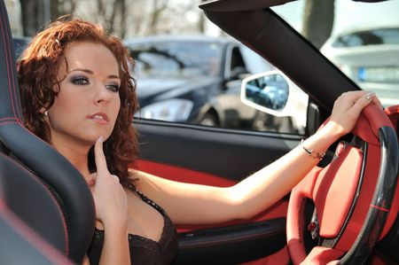 Young beautiful thoughtful woman sitting in sport car - red interior detail photo