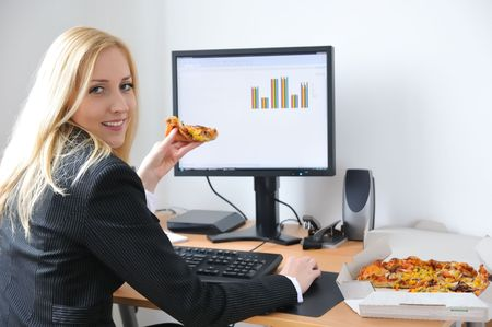 Young business woman siting at work table and eating pizza Stock Photo - 4736485