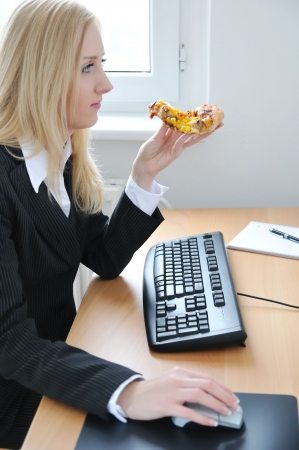 unhealthy lifestyle: Young business woman concentrating on work and eating pizza