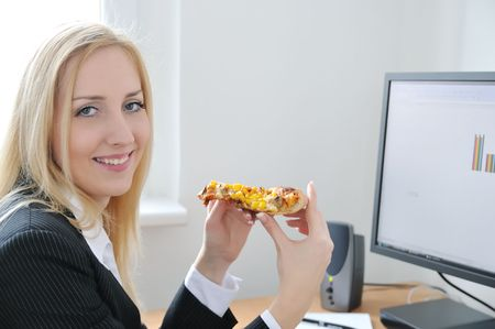Young smiling business person on work place eating pizza Stock Photo - 4736475